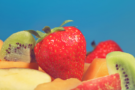 Mixed fruit kiwi strawberries and mellon on a blue background