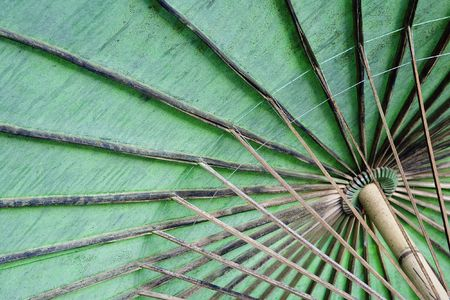 The underside of a cotton umbrella with colorful painted flowers showing the bamboo ribs handmade at the Umbrella Making Centre in Bo Sang, Thailand. Bo Sang is known as the Umbrella Village but is also known for its silk, pottery and wood carving factori