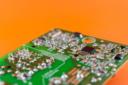 green circuit board with integrated chip and electronic component on orange background Banco de Imagens