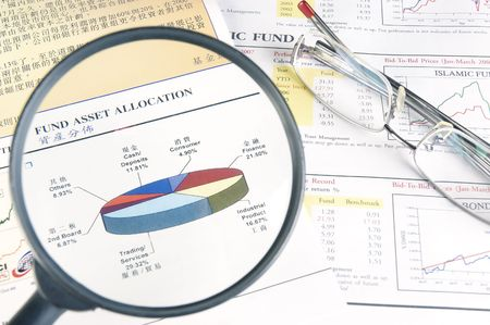 Reading a financial fact sheet with magnifying glass.  Stock Photo