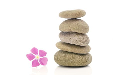 A pink flower with a stack of pebbles.