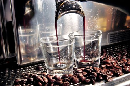 A coffee maker starting to fill up two glasses with coffee beans spreading accross.