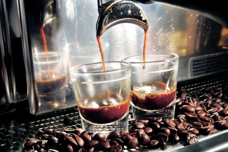 A coffee maker filling up two glasses of coffee with coffee beans spreading across.