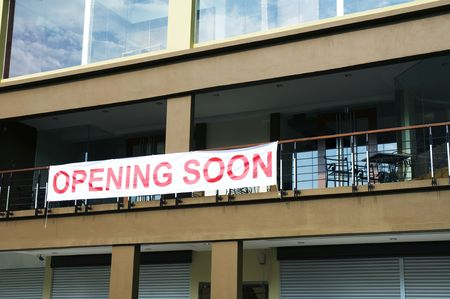 An Opening Soon banner on a newly completed building.
