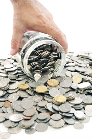 money jar: Pouring coins out of a money jar. Stock Photo