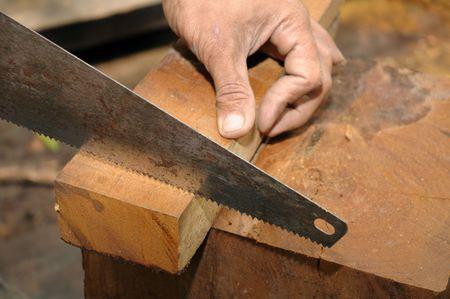 Closeup of a carpenter sawing a wood. Stock Photo