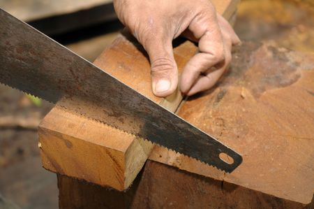 Closeup of a carpenter sawing a wood. Stock Photo