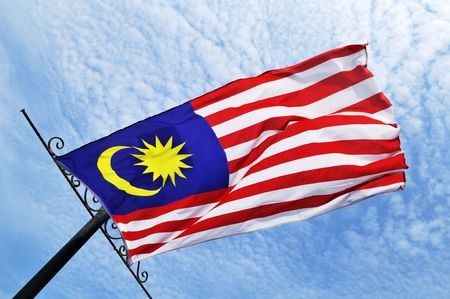 Malaysian flag blowing in the wind against blue sunny sky. Stock Photo