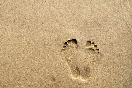 Footprints on sandy beach with copy space for background use. Stock Photo