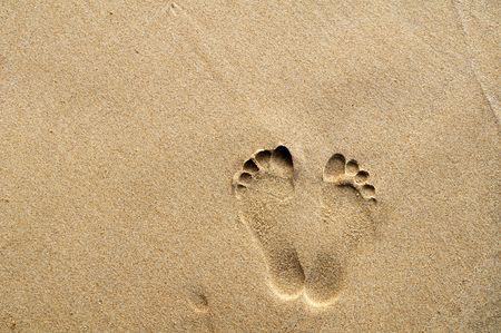 huella pie: Utilizan la huellas en la playa de arena con espacio de copia para el fondo. Foto de archivo