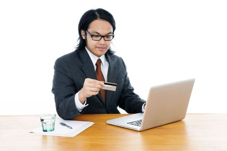 Young business executive holding credit card and using laptop over white background.  photo