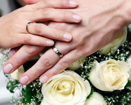 truelove: Closeup of newlywed couple holding hands over bouquet of flowers.