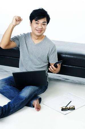 Portrait of an excited young man sitting on floor with laptop.