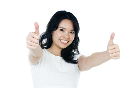 Portrait of an attractive young woman giving thumbs up against white background. Stock Photo