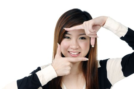Portrait of an attractive young woman showing picture frame with her fingers over  white background. Stock Photo