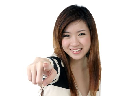 Portrait of an excited young woman pointing at camera on white background.