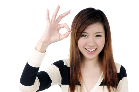 Portrait of an attractive woman showing OK sign over white background.