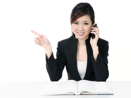 Portrait of an attractive young businesswoman talking on cellphone and pointing towards copypace, isolated on white background. Stock Photo