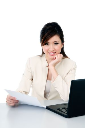 Portrait of a happy young businesswoman at office desk, isolated over white background.