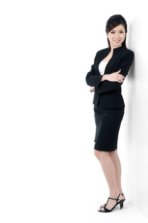 Portrait of a beautiful young businesswoman leaning against white wall.