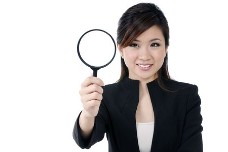 Portrait of a beautiful young businesswoman holding and looking at magnifying glass, over white background. Stock Photo