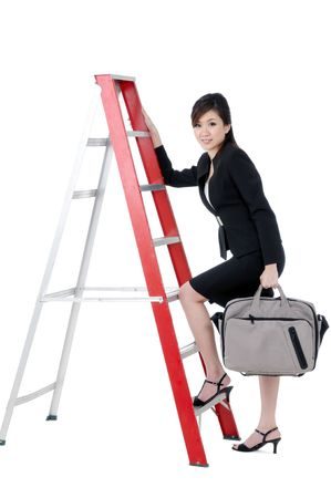 Portrait of a beautiful young businesswoman climbing up ladder with bag in hand, isolated on white background.