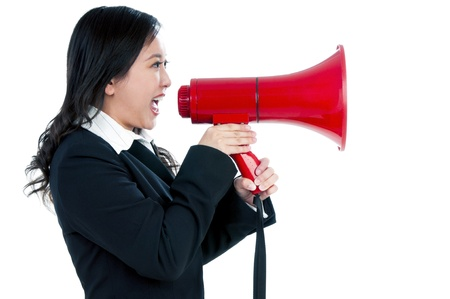 loudhailer: Portrait of an attractive businesswoman using a megaphone over white background.