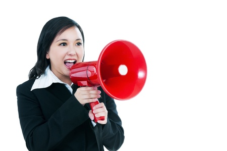 Portrait of an attractive businesswoman using a megaphone over white background. photo