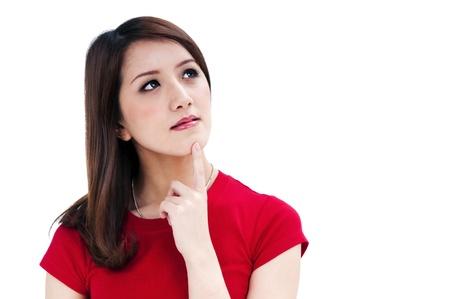 Close-up van een aantrekkelijke jonge vrouw denken, geïsoleerd op een witte achtergrond.