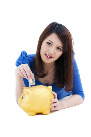 Portrait of a cute young woman putting money into piggy bank over white background.