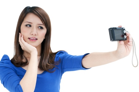 Portrait of a cute young woman taking a self portrait over white background.