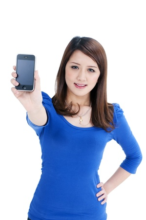 Portrait of a cute young woman holding out cellphone over white background. Stock Photo