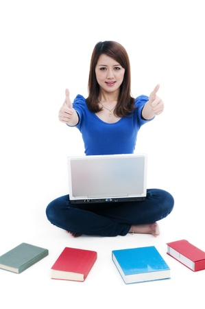 spread around: Portrait of a cute student with laptop and books spread around, giving thumbs up sign over white background. Stock Photo