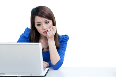 Portrait of a pensive woman using laptop  over white background. Stock Photo