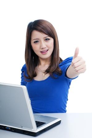 laptop asian: Retrato de una mujer joven y atractiva con la computadora port�til y el letrero con el pulgar hacia arriba sobre fondo blanco.