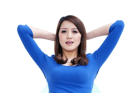 Portrait of an attractive young woman relaxing with hands behind head over white background.