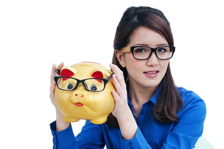 Portrait of a cute young woman holding piggy bank against white background.