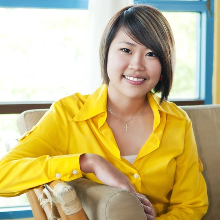 Portrait of a beautiful young woman sitting on sofa.
