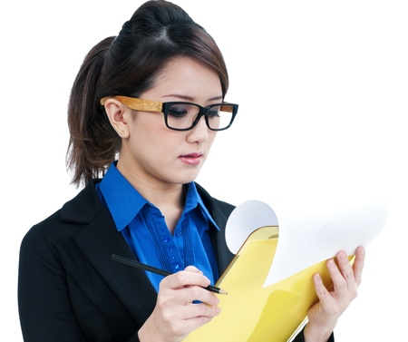 Portrait of an attractive young businesswoman holding and looking at clipboard, isolated on white background. photo