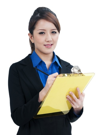 Portrait of a cute young businesswoman writing on clipboard, isolated on white background. photo
