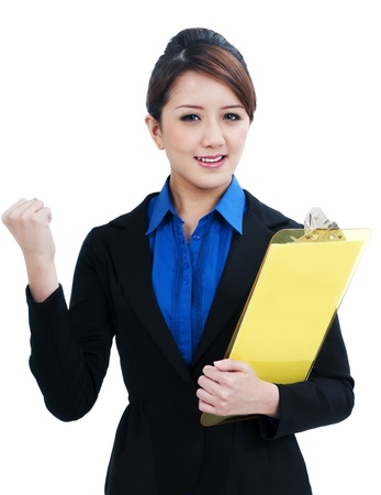 Portrait of a beautiful young businesswoman clenching her fist and holding clipboard, isolated on white background. photo