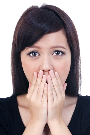 Portrait of a shocked young female covering mouth with her hands, isolated on white background.