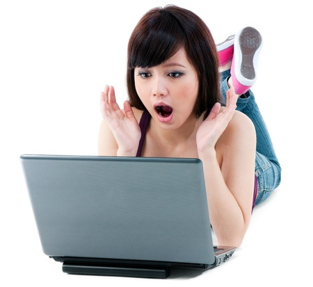 Portrait of a young Asian woman looking amazed at laptop over white background. photo