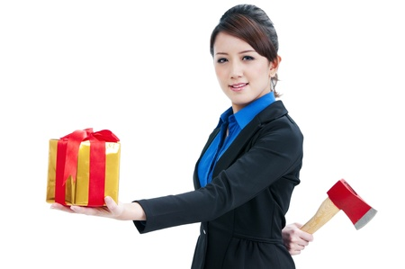 Businesswoman presenting a gift box in front and holding an ax behind her back, isolated on white background.  photo