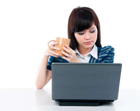 Portrait of a young Asian woman holding cup and looking at laptop over white background. photo