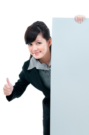 Portrait of a young Asian businesswoman giving thumb up gesture and holding a blank billboard against white background  photo