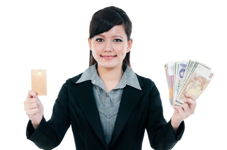 cash cow: Portrait of a cute young Asian businesswoman holding credit card and money, isolated on white background  Stock Photo