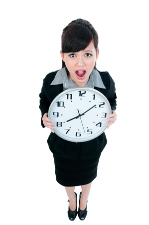 time out: Portrait of a cute young Asian businesswoman holding a clock, isolated on white background.