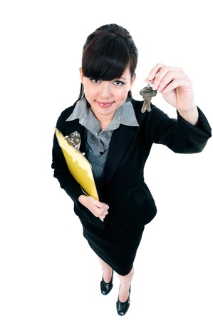 Full length portrait of a cute young Asian businesswoman holding clipboard an keys against white background. photo