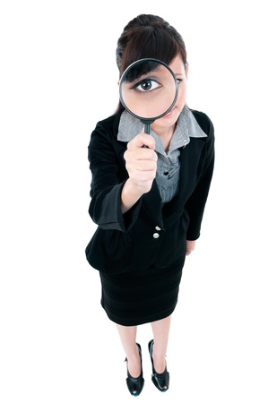 investigating: Portrait of a young Asian businesswoman looking through magnifying glass, over white background. Stock Photo